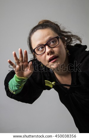 thirty something brunette woman with glasses cupping her hand to her ear - stock photo
