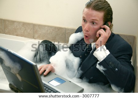 Thirty something business man in bubble bath with cellphone and laptop computer. - stock photo