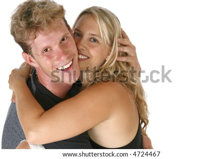 Thirty something caucasian couple hugging and smiling.
