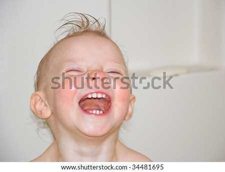 This baby girl is laughing in this facial photo in a bathtub with a little curl on top of her head.  Very contagious laughter and a shot of total happiness.