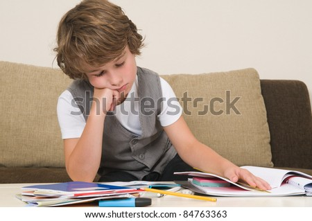 This boy is very tired of doing his homework, he fell asleep - stock photo