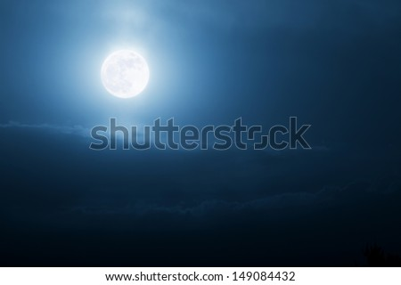 This bright, shining moonrise illuminates the night time sky with the brilliance of the sun. Would make a wonderful background for Halloween or any magical tale. - stock photo