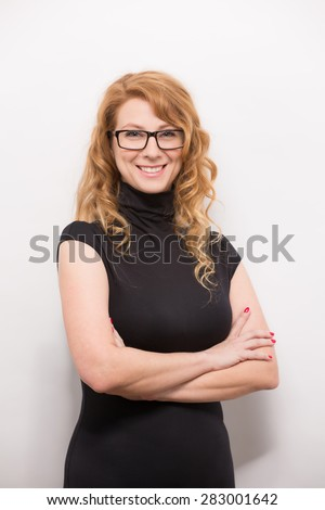 This businesswoman dressed in a black dress is smiling, because experience, training or licensing may be needed for her. She is considering to start her own business. - stock photo