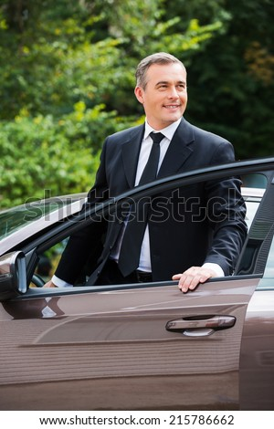 This car is perfect for me. Cheerful mature man in formalwear looking away and smiling while getting out from car - stock photo