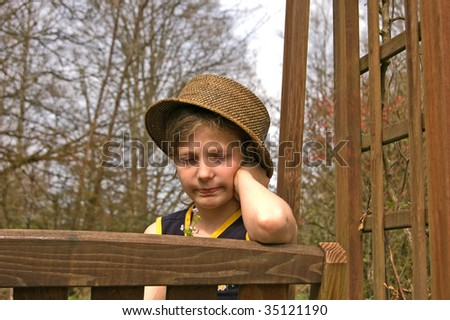 This child sitting on a garden swing is wearing a hat and looking at small flowers.  Her facial expression is one of sadness and being upset. - stock photo
