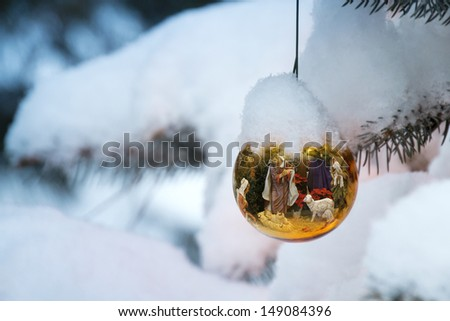 This Christmas Tree Ornament brightly reflects a Nativity Scene with the newborn baby Jesus on a snow Christmas morning outdoors. - stock photo