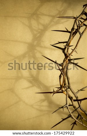 This Crown of Thorns against parchment paper represents Jesus' Crucifixion on the Cross, dying and then rising on Easter Sunday.  The shadow of the Crown of Thorns on the parchment adds to the visual. - stock photo