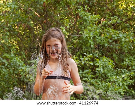 This cute girl is playing in the sprinkler in summer to cool off with lots of green leaves in the background.  Fun childhood summer moments. - stock photo