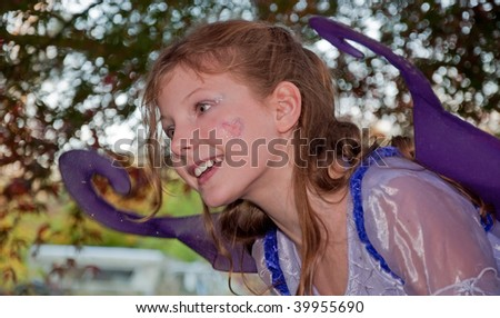 This cute 9 year old girl is wearing a ferry princess costume in a pose trying to flying with her wings. - stock photo