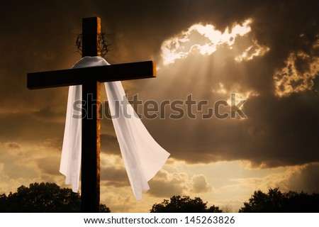 This dramatic lighting with storm clouds breaking and sunshine bursting through makes a great Easter photo illustration of Jesus dying on the cross and rising again. - stock photo