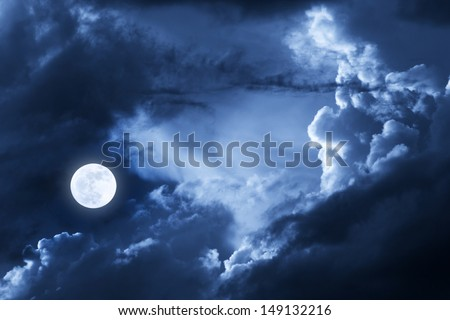 This dramatic photo illustration of a nighttime scene with brightly lit clouds and large, full, Blue Moon would make a great background for many uses. - stock photo