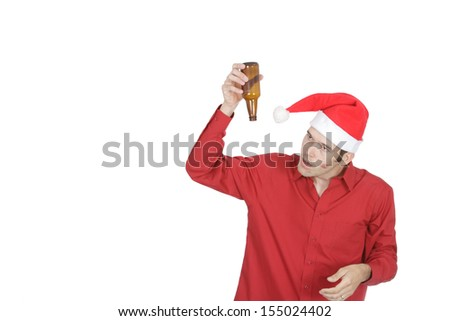 This drunk white collar worker looks confused that his beer bottle is empty. Wearing a santa hat with a lipstick kiss on his cheek he looks disheveled and unprofessional. - stock photo