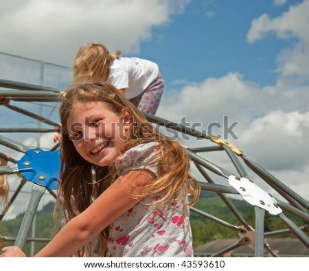 This eight year old Caucasian girl is smiling and happy while playing outdoors on playground equipment on a windy, cloudy day. - stock photo