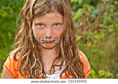 This elementary aged Caucasian girl is playing outdoors and making a goof pouty face.  Her hair is tangled and wind blown, and she has piercing green eyes. - stock photo