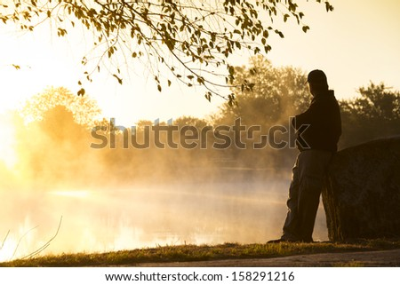 This foggy morning and quite lake makes for an inspirational location for this adult male to contemplate life's challenges and rewards in a quiet setting. - stock photo