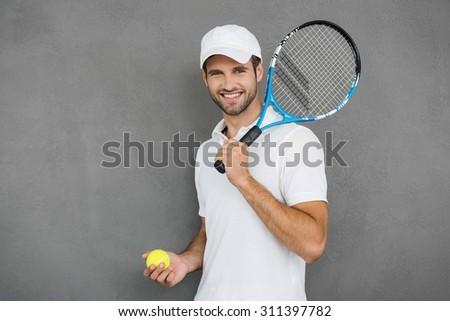 This game is more than hobby! Happy young man in sports clothes carrying tennis racket on his shoulder and smiling while standing against grey background - stock photo