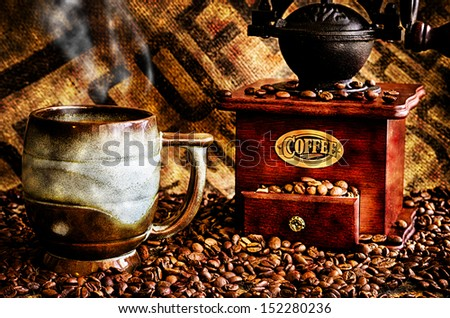 This image is a closeup of a cup of steaming hot coffee with coffee beans, coffee grinder, and coffee beans bag in background. - stock photo