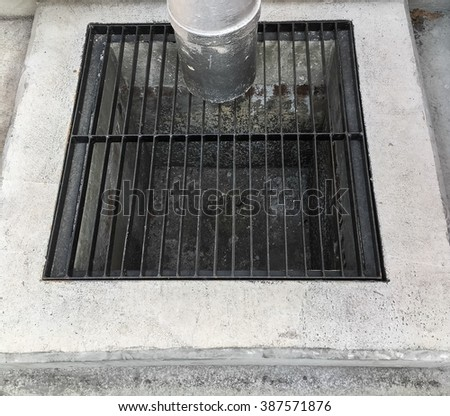 This image is close up the manhole with black steel grating on top in the construction site.