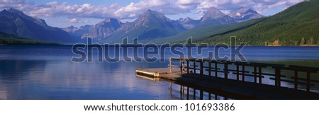 This is a boat dock at Lake McDonald. The blue water of the lake surrounds the dock with mountains in the background. - stock photo