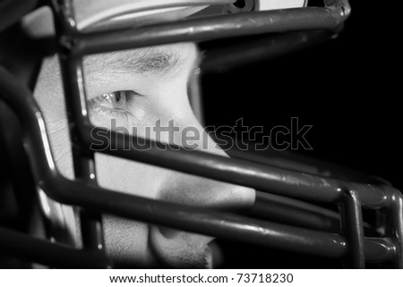 This is a close up, high contrast black and white image of a young man wearing a football helmet and looking away from the camera with an intense look in his eye. - stock photo