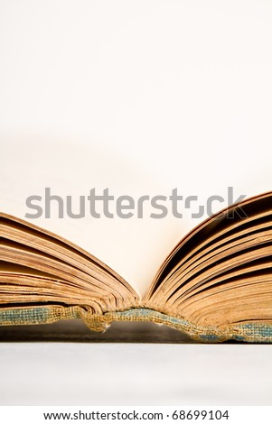 This is a close up photo of an old open book with it's pages laid out. Shot on a white background.