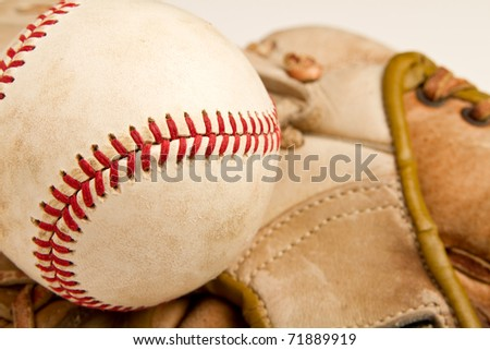 This is a close up shot of an old baseball with an old baseball glove in the background. Shot with a shallow depth of field.
