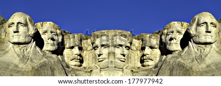 This is a digitally created image. It is a double image of Mount Rushmore connected at its center against a blue sky. - stock photo