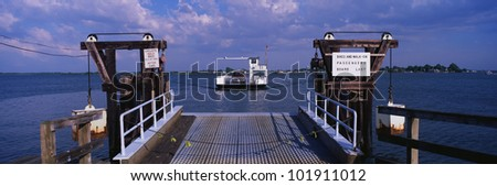 This is a dock in Maryland. You can see a ferry in the distance that has just left the dock. - stock photo