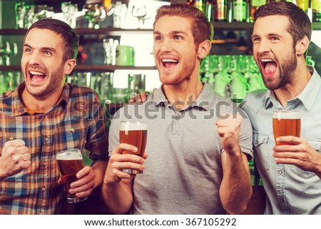 This is a goal! Three happy young men in casual wear holding glasses with beer and gesturing while standing at the bar counter and looking away - stock photo
