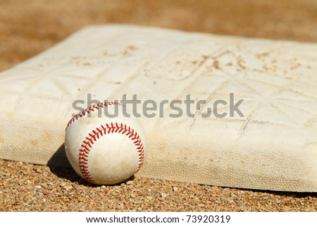 This is a high contrast shot of an old baseball sitting next to a dirty base on a baseball field.