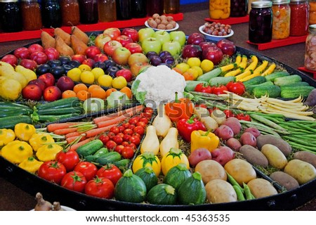 This is a large round display of many fruits and vegetables, potatoes, squash, cucumbers, apples, plums, cauliflower, green beans, tomatoes, peppers, pears and more.