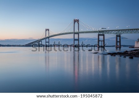 This is a long exposure morning sunrise image of the Newport Bridge from Taylor Point near Jamestown, Rhode Island, USA. This is a horizontal image. / Newport Bridge Twilight - stock photo