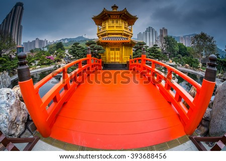 This is a low angle fish-eye landscape-orientation shot of Golden pavilion at Nan Lian garden, one of the landmarks of Hong Kong. In this photo, you will see the pavilion at the end of the red bridge. - stock photo
