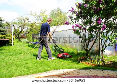 This is a men mowing the grass.