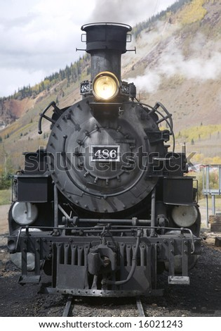 This is a photo of the front of an old steam locomotive getting ready to pull a group of passenger cars through the mountains of Colorado. - stock photo