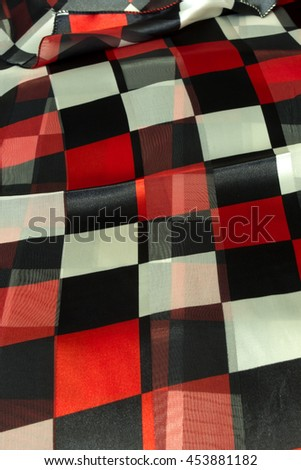 This is a photograph of a red,white and black square patterned polyester scarf