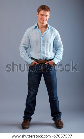 This is a photograph of a young man standing with his hands in pocket - stock photo