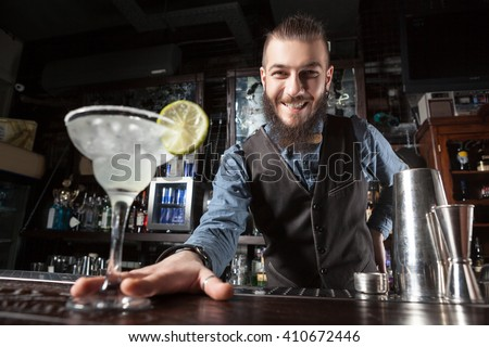 This is a photograph of barman serving cocktail margarita.