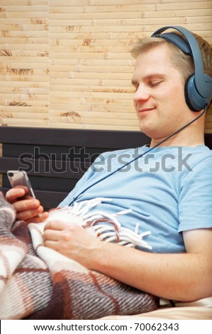 This is a photograph of laying young man listening music - stock photo