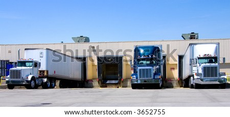 This is a picture of 18 wheeler semi trucks loading at a warehouse building. - stock photo