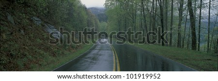 This is a rain soaked road showing bad weather. It is called the Foothill Parkway and is surrounded by green trees. - stock photo