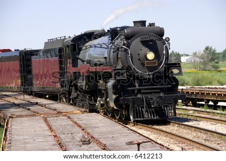 This is a restored steam locomotive on the tracks ready for an excursion. with numbers removed