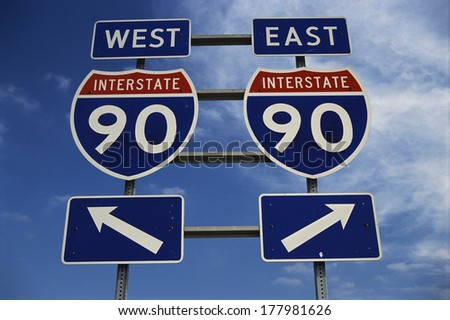 This is a road sign on the New York State Freeway. It points out the direction for Route 90 to go east or west. The signs are blue, red and white against a blue sky. - stock photo