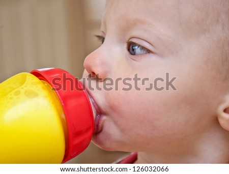 This is a side view closeup of a toddler girl drinking milk out of a sippy cup.  She is a Caucasian with blue eyes. - stock photo