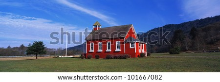 This is a small school house. It is painted a bright red with white trim on the windows. The sky is blue and it is surrounded by green grass, bushes and trees. - stock photo