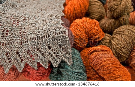 This is a still life of beautiful skeins of colorful yarns, and a portion of a handmade natural colored scarf.  Oranges, browns, greens, textile materials. - stock photo