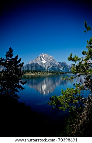 This is a toned image of the Grand Teton Mountain range reflecting in a lake, shot through some trees. - stock photo