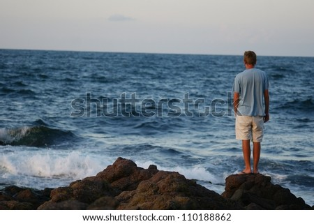 This is a view of man sitting on the rock by the sea.