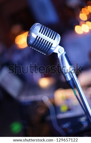 This is a vintage microphone with a DJ Table in the background. I shot this picture during a big party. - stock photo