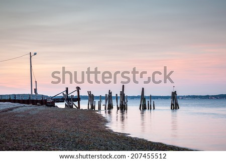 This is a warm colorful sunset seascape of the Prudence Island ferry landing from Bristol in Rhode Island, USA. / Sunset Ferry Dock Landscape - stock photo